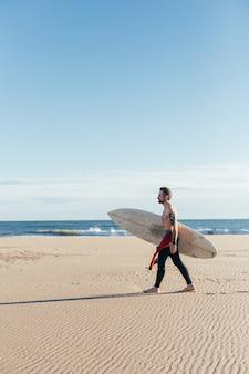 따뜻한 여름날에 빈 해변에서 서핑 보드와 중간 나이 든 남자를 맞추십시오.