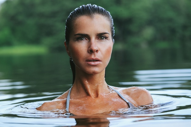 Подтянутая модель в сером бикини на озере