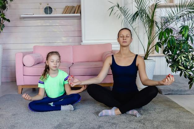 リビングルームでヨガや瞑想をしている母と娘に合います。ホームスポーツ。家族が家から一緒にスポーツをしています。ヨガと家族の概念。