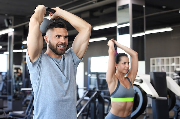 Fit and muscular couple focused on lifting a dumbbell during an exercise class in a gym.