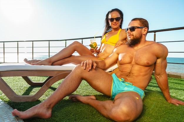 Fit muscular couple in swimwear relaxing near the pool