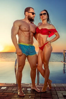 Fit muscular couple in swimwear relaxing near the pool