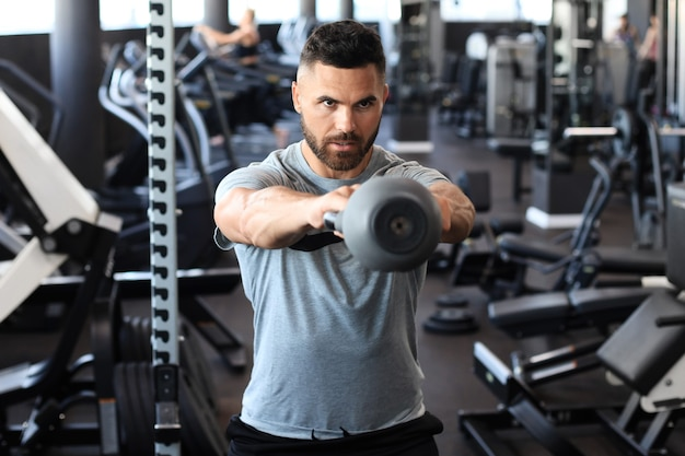 Fit and muscular indian man focused on lifting a dumbbell during an exercise class in a gym.