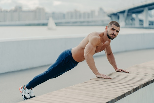 Fit muscular man does plank push up exercise leads healthy lifestyle wears sport trousers and sneakers poses outdoor near bridge. motivated sportsman pushing hard. sport, motivation and determination