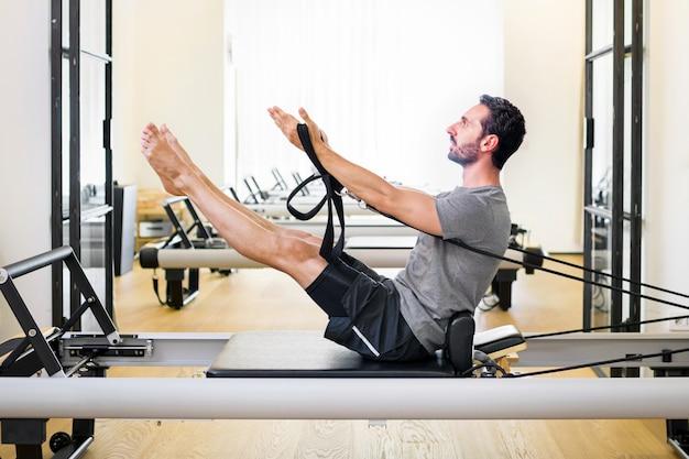 근육질의 남자가 체육관에서 리포머에게 필라테스 운동을 하여 카피스페이스가 있는 측면 보기에서 코어와 복부 근육을 강화합니다.