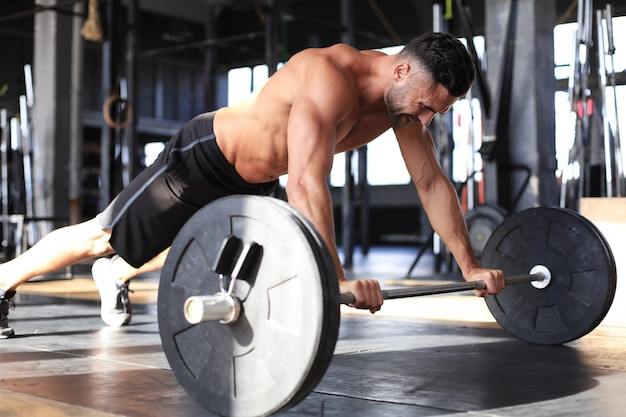 Fit and muscular man doing horizontal push-ups with barbell in gym.