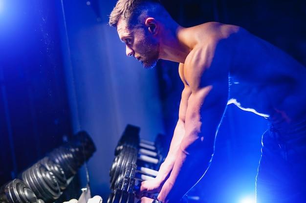 ダンベルで運動している筋肉質の男性に合います。暗い背景にウェイトを持ち上げる筋肉の若い男。ブルーライトフィルター、裸の胴体。閉じる。