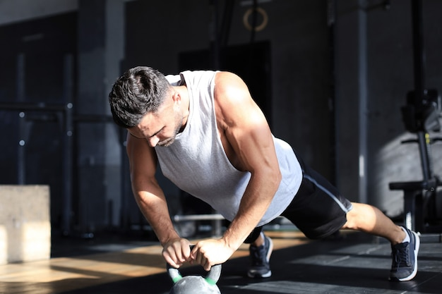 Fit and muscular man focused on lifting a dumbbell during an exercise class in a gym.