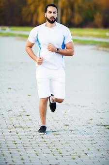 外で実行されている筋肉男に合うフィットネスとスポーツコンセプト