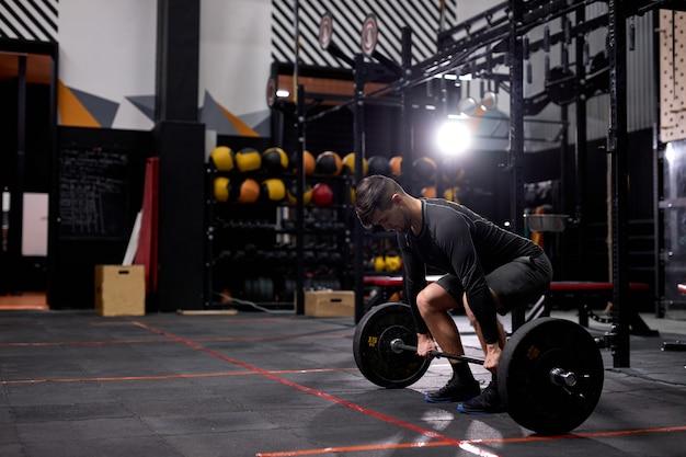 一人でスポーティーな服を着て、ジムでクロスフィットスイングトレーニングハードコアトレーニングのために重い体重を保持している大きな筋肉を持つ筋肉質の男性にフィットします。肖像画