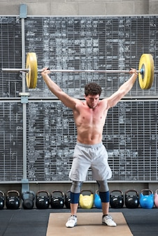 Fit muscular weightlifter doing crossfit training