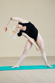 매트에서 운동할 때 측면 굴곡을 하고 카메라를 바라보는 근육질의 여성
