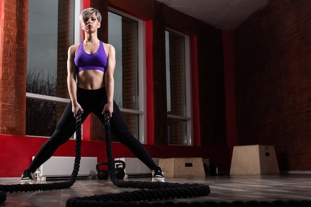 Fit and muscular woman exercising with battling ropes at fitness studio. female athlete doing battle rope workout at gym.