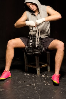 Fit muscular young boxer putting on his gloves