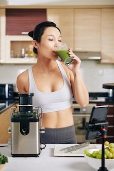 彼女が作ったおいしい新鮮な果物や野菜ジュースを飲む筋肉の若い女性に合う