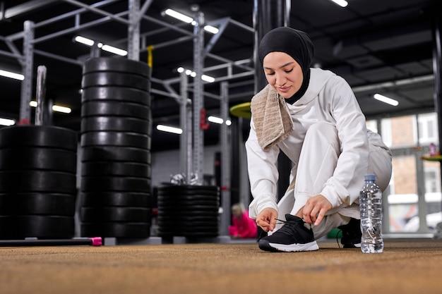 フィットするイスラム教徒の女性は、スポーツの練習の前にスニーカーにひもを結び、ジムでトレーニングを行い、白いスポーツのヒジャーブを身に着け、若いアラビアの女性が健康的なライフスタイルをリード
