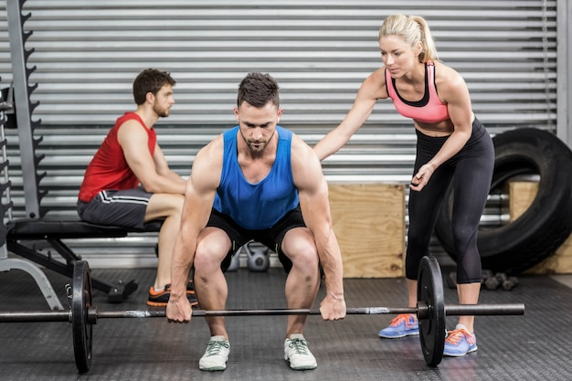 Fit people doing exercises at crossfit gym