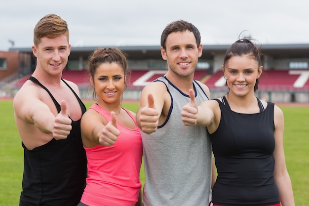 Fit people gesturing thumbs up on ground against the stadium