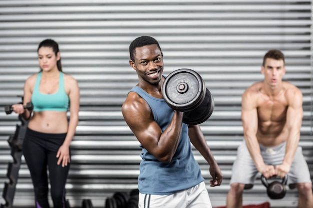 Fit people lifting dumbbells at crossfit gym