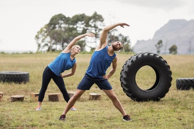 Подходящие люди, выполняющие упражнения на растяжку в учебном лагере