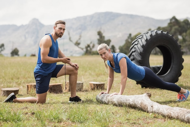 Fit performing pushup exercise while man measuring time in boot camp