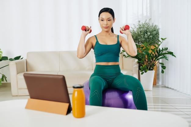 フィットネスボールに座って、タブレットでビデオガイドを見て、ダンベルで運動をしているかなり若いアジアの女性にフィットします