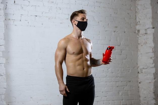 Соответствовать. профессиональная тренировка спортсмена мужского пола на предпосылке кирпичной стены нося лицевую маску. спорт во время карантина из-за всемирной пандемии коронавируса. молодой человек, практикующий в тренажерном зале, безопасно с использованием оборудования.