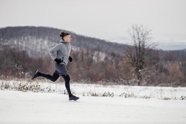 겨울에 눈 위에서 자연 속에서 달리는 주자. 유산소 운동, 건강한 생활 방식, 겨울 피트니스