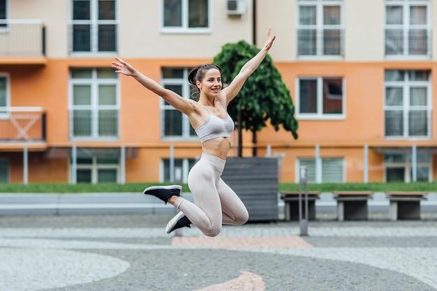 フィットランニングの若い女の子のアスリートが空中を飛んでいる間、走っている間、都市で走っている空中でより糸を作ります。