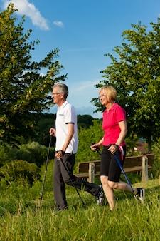 年配のカップルに自然の中でハイキングを楽しむノルディックウォーキングスティックを装着