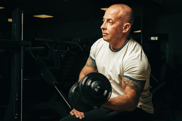 Fit senior man exercising with dumbbells in a gym
