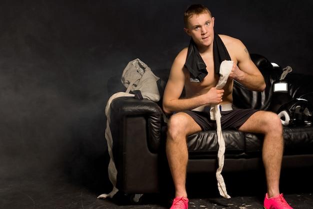 筋肉質の体格を持つ真面目な若いボクサーにフィットし、黒い革のソファに手を包帯を巻く