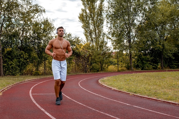 Fit shirtless male with white shorts and headphones running on a track