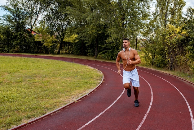 Fit shirtless man with white shorts and headphones around his neck running on a track