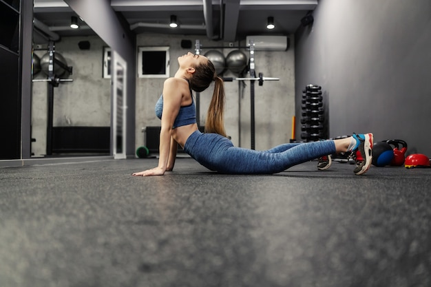 Fit and slender woman stretches the muscles of the body core and abdomen