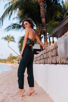 Fit slim donna caucasica sulla spiaggia tropicale in occhiali da sole, top e pantaloni in denim