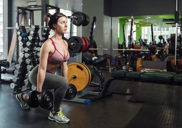 체육관에서 아령으로 돌진을 연습하는 운동복에 슬림 한 여성을 맞 춥니 다.