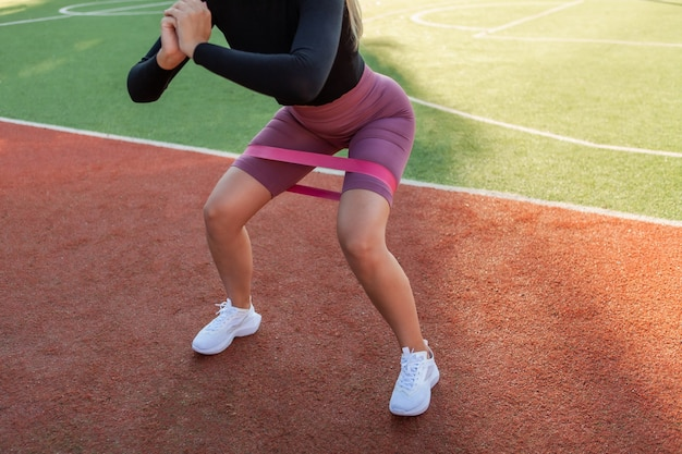 Fit slim woman practicing squats with fitness rubber bands at stadium