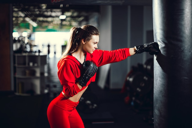 Fit slim young beautiful brunette woman boxing in sportswear. dark dim light.