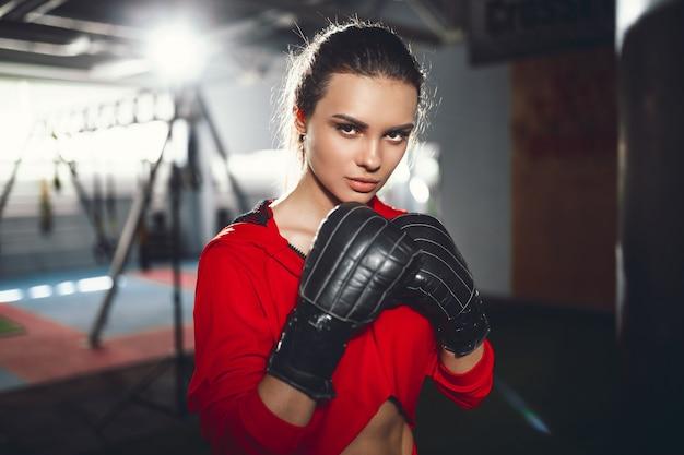 Fit slim young beautiful brunette woman boxing in sportswear. dark dim light.