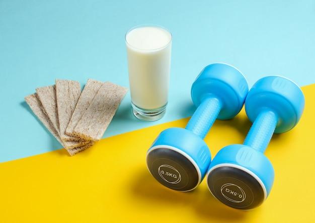 痩身コンセプトにフィット。ダンベル、ケフィアのガラス、青黄色のテーブルにダイエットクリスプブレッド