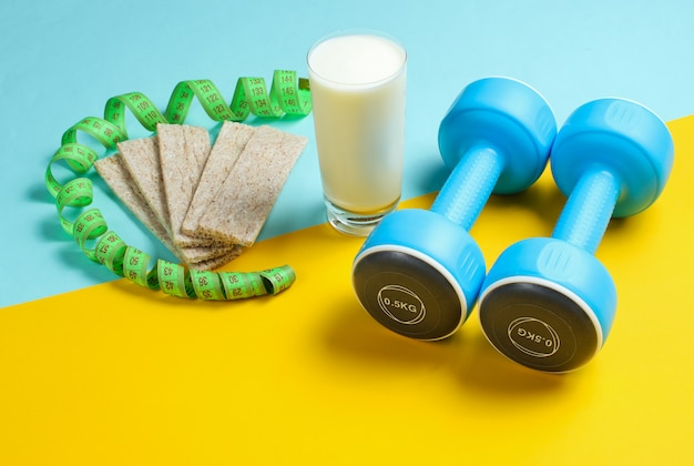 痩身コンセプトにフィット。ダンベル、定規、ケフィアのガラス、青黄色のテーブルにダイエットパン