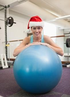 운동 공에 기대어 산타 모자에 웃는 갈색 머리에 맞게