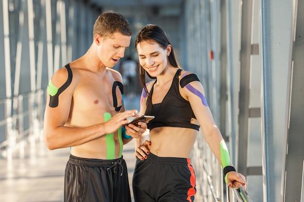 腰に手を当てて笑顔のブルネットの女性とスマートフォンを見てチャットしている男性にフィットします