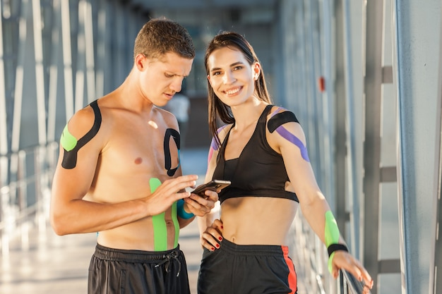Fit smiling brunette woman with hand on waist and man looking at smartphone and chatting