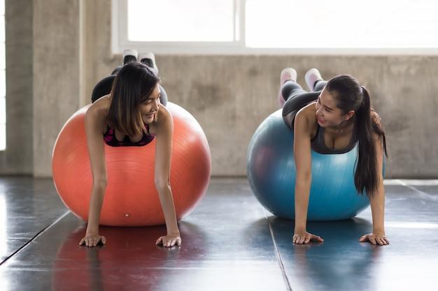 笑顔のスポーティなレズビアンlgbtのカップルや友人を、ジムでフィットネスボールを使って運動する板の位置に合わせます。ボディービルと健康的なスポーツライフスタイルのために一緒に運動している女性。