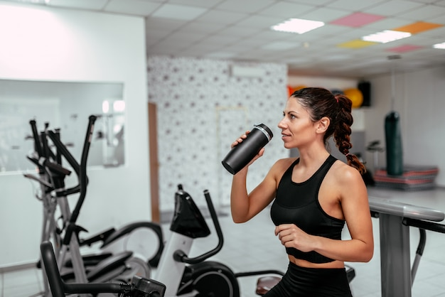 Fit smiling woman drinking water from bottle while exercising on static bike at the gym.