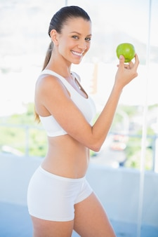 Fit smiling woman holding green apple