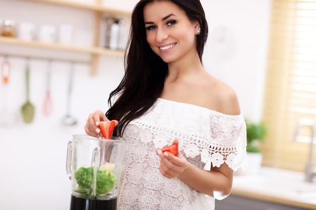 현대 부엌에서 건강한 스무디를 준비하는 맞는 웃는 젊은 여자