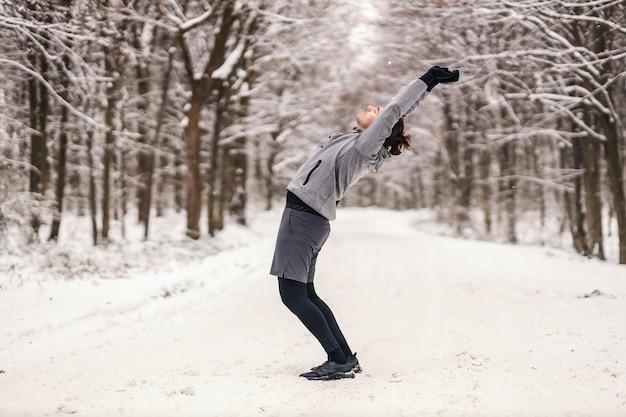 森の雪の降る冬の日にウォームアップ運動をしているスポーツマンに合いましょう。冬のフィットネス、健康的な生活